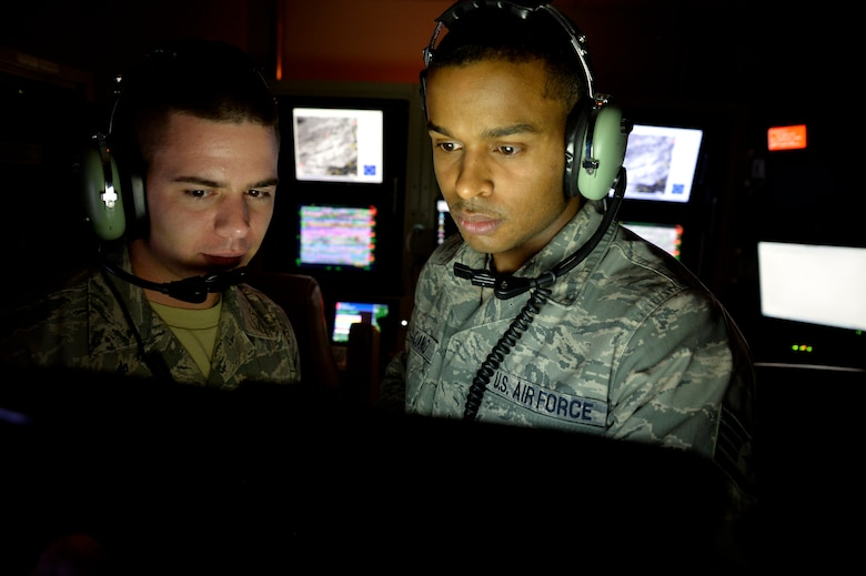 Airman First Class Ryder Luzadder, 432nd Aircraft Communications Maintenance Squadron communications technician, left, and Staff Sgt. Jose Feliciano, 432nd ACMS communications technician, look over technical orders for a ground control station May 28, 2014. The 432nd ACMS is the only squadron of its kind in the Air Force and is responsible for providing 24/7, 365-day maintenance support to the communication infrastructure that supports the wing's global remotely piloted aircraft operations. (U.S. Air Force photo by Staff Sgt. Adawn Kelsey/Released)