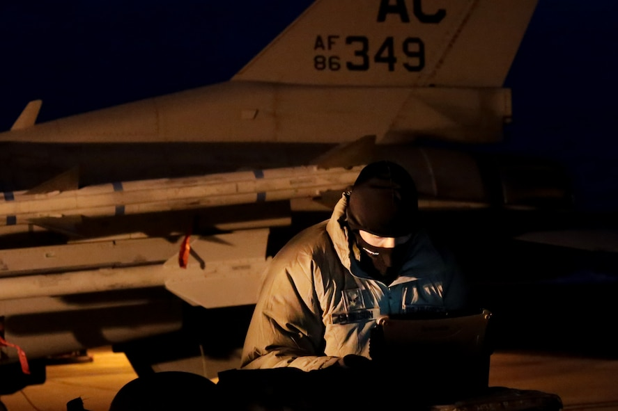 U.S. Air Force Airman 1st Class Christopher Garrison, an F-16 crew chief from the New Jersey Air National Guard's 177th Fighter Wing, goes over technical orders prior to a training mission early in the morning at Atlantic City Air National Guard Base, N.J., Jan. 9, 2015. Airmen from the 177th Fighter Wing took part in JAN ME EX 15-01, a mission employment exercise that tested the Wing's sortie generation capabilities. (U.S. Air National Guard photo by Tech. Sgt. Matt Hecht/Released)