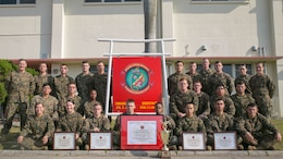 "Marines with Headquarters Regiment stand with their maintenance readiness awards from all four quarters and the overall 2014 fiscal year on Camp Kinser, Dec. 31. Headquarters Regiment, 3rd Marine Logistics Group, III Marine Expeditionary Force maintained an overall maintenance readiness of 90% or higher throughout the entire year of 2014. ""My success comes from the success of my Marines,"" said Col. Edmund J. Bowen, the regiment's commanding officer, from Staten Island, New York."
