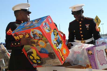 "Lance Cpl. Gentres Anderson, from Pensacola, Florida, and Sgt. Sheldon Curry, from Montgomery, Alabama, help bring toys to the donation bins for the Marines' Toys for Tots Program in Montgomery, Alabama, Dec. 13, 2014. The program found its roots in 1947 Los Angeles when Marine Maj. Bill Hendricks, a reservist, collected more than 5,000 toys to help his community. The Marine Corps formally adopted the program the very next year, and it has continued to this day. ""This is a great chance for us to give back to the community and help those families in need,"" said Curry, who has lived his whole life in Montgomery. ""I come from a family that didn't have anything. We got fruit – apples, oranges – for Christmas. This makes a difference."" ""Those kids that don't have anything,"" Curry added. ""They really appreciate just having a gift."""