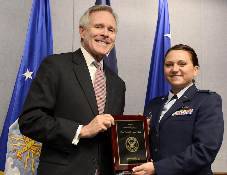 Secretary of the Navy Ray Mabus presents a plaque to Capt. Dana Lyon during the naming ceremony of the Motor Vessel Capt. David I. Lyon, Jan. 14, 2015, in the Pentagon.  The plaque lists Dana Lyon as the ship's sponsor.  The vessel was named in honor of Capt. David Lyon, who was killed in action Dec. 27, 2013, while serving in support of Operation Enduring Freedom.  (U.S. Air Force photo/Scott M. Ash)