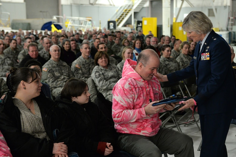 Brig. Gen. Carolyn J. Protzmann, N.H. Air National Guard commander, presents Shawn Riley a flag flown for his wife, Lt. Col. Stephanie Riley, during a posthumous retirement ceremony in Hangar 254, Jan. 10. The flag for Riley, who passed away Dec. 29 at the age of 47, was flown at the behest of the N.H. Governor Maggie Hassan. (U.S. Air National Guard photo by Tech. Sgt. Mark Wyatt)