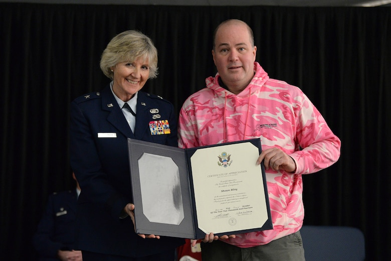 Brig. Gen. Carolyn J. Protzmann, N.H. Air National Guard commander, and Shawn Riley pose for a photo after a spouse presentation certificate of appreciation during a posthumous retirement ceremony for his wife, Lt. Col. Stephanie Riley, in Hangar 254, Jan. 10. Riley, who passed away Dec. 29 at the age of 47, was an occupational health nurse for the N.H. National Guard and longtime member of the 157th Medical Squadron. (U.S. Air National Guard photo by Tech. Sgt. Mark Wyatt)