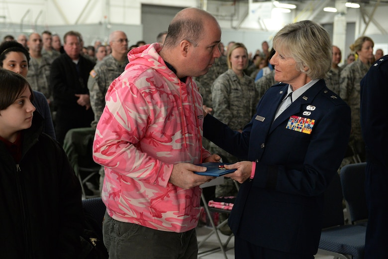 Brig. Gen. Carolyn J. Protzmann, N.H. Air National Guard commander, presents Shawn Riley the Legion of Merit Medal during a posthumous retirement ceremony for his wife, Lt. Col. Stephanie Riley, in Hangar 254, Jan. 10. Riley, who passed away Dec. 29 at the age of 47, was an occupational health nurse for the N.H. National Guard assigned to Joint Force Headquarters in Concord. (U.S. Air National Guard photo by Tech. Sgt. Mark Wyatt)