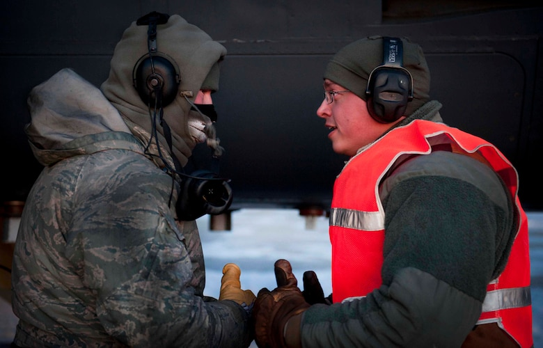Senior Airman Taylor Lancaster speaks to a maintenance Airman Jan. 9, 2014, on Minot Air Force Base, N.D. Lancaster ensures his jet is fixed and prepared to take off before its flight time. Lancaster is a 5th Aircraft Maintenance Squadron aircraft crew chief. (U.S. Air Force photo/Airman 1st Class Sahara L. Fales)