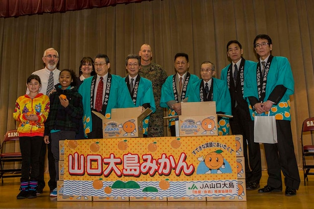 Members of the local Iwakuni agricultural and societal cooperative associations pose for a photo with Lt. Col. Mike Carreiro, executive officer of Marine Corps Air Station Iwakuni, Japan, and members of the Matthew C. Perry Elementary School's faculty and student body during the school's mikan presentation inside the school's gymnasium, Jan. 13, 2015, aboard station. The purpose of the event was to strengthen the bond between Iwakuni City residents and M.C. Perry students. Members of the associations presented M.C. Perry Elementary School with 20 boxes of mikans from Suo-Oshima Island.