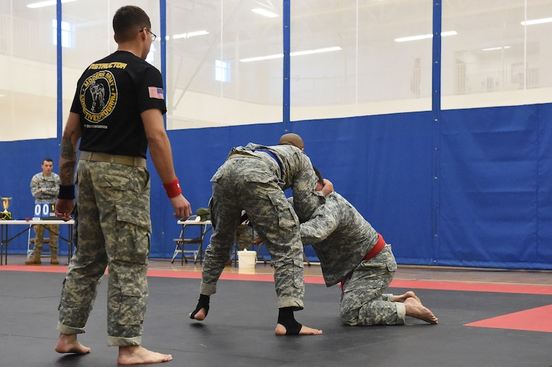 A combatives training instructor judges two U.S. Army 743rd Military Intelligence Battalion Squadron members as they compete for commander's cup points during a combatives tournament at the Buckley Fitness Center Jan. 15, 2015, on Buckley Air Force Base, Colo. The army battalion hosts the tournament every year to hone hand-to-hand combat training techniques while engaging in friendly competition. (U.S. Air Force photo by Airman 1st Class Samantha Saulsbury/Released)