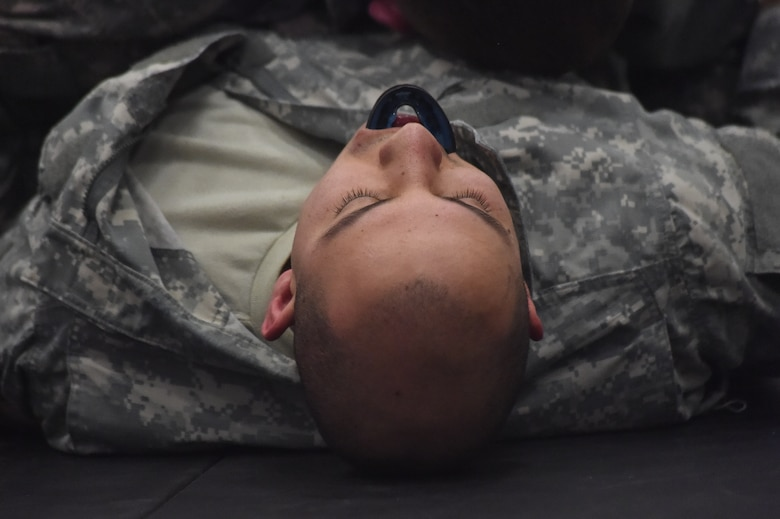 A U.S. Army 743rd Military Intelligence Battalion member lies defeated after competing in a combatives tournament held at the Buckley Fitness Center Jan. 15, 2015, on Buckley Air Force Base, Colo. The army battalion hosts the tournament every year to hone hand-to-hand combat training techniques while engaging in friendly competition. (U.S. Air Force photo by Airman 1st Class Samantha Saulsbury/Released)