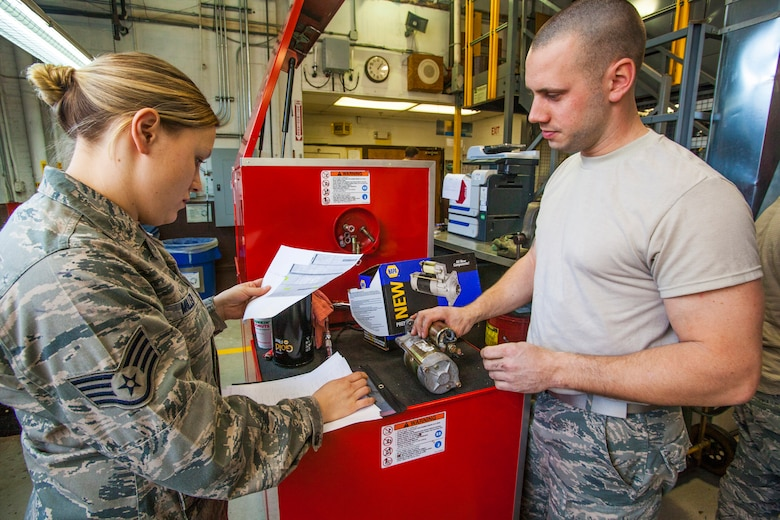 Senior Airman Keith Miller, right, describes to Staff Sgt. Danielle Miller what broke on the starter for a six-passenger pickup truck at the 108th Wing Vehicle Maintenance Shop at Joint Base McGuire-Dix-Lakehurst, N.J., Jan. 11, 2015. Staff Sgt. Miller is a vehicle management and analysis technician with the 108th Vehicle Management Section, while Senior Airman Miller is a general purpose mechanic with the 108th Vehicle Maintenance Shop. Vehicle maintenance is part of the 108th Logistics Readiness Squadron, New Jersey Air National Guard. (U.S. Air National Guard photo by Master Sgt. Mark C. Olsen/Released)