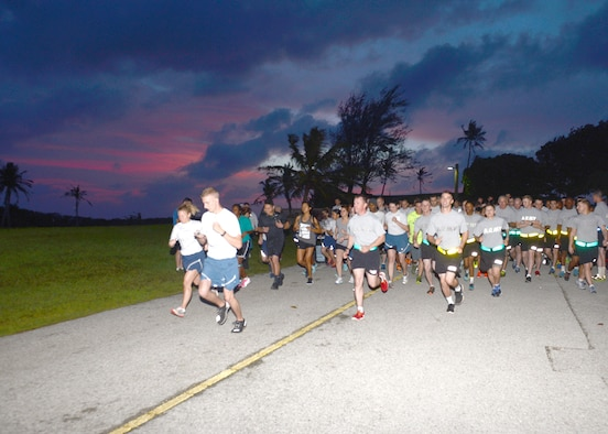 Team Andersen members get the New Year's Hustle 5K run started during the pre-dawn hours Jan. 14, 2015 at Andersen Air Force Base, Guam. Nearly 100 Andersen Airmen, U.S. Army Soldiers from Task Force Talon, civilians and family members took part in the run that required runners to run from the Palm Tree Golf Course Driving Range to the Guam Air National Guard's 254th RED HORSE Squadron headquarters and back. (U.S. Air Force photo by Tech. Sgt. Zachary Wilson/Released.)