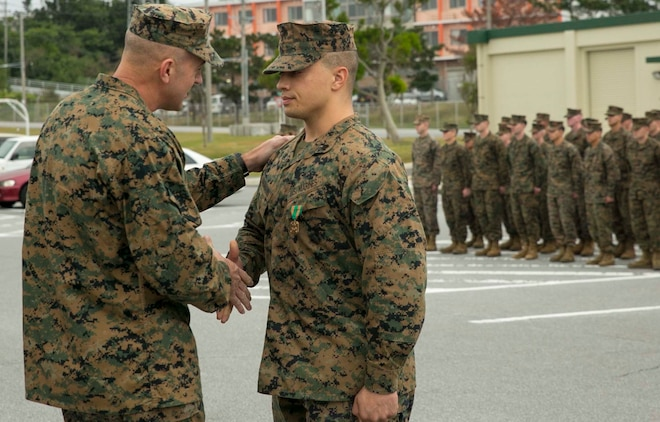 "Col. Lance A. McDaniel, left, congratulates Sgt. Jacob J. Baumann Jan. 14 on receiving the Navy and Marine Corps Achievement Medal for potentially saving the life of a local Japanese gentleman. ""Heroism often involves an ordinary man doing extraordinary things for others,"" said McDaniel from Waco, Texas. ""Recently Sgt. Baumann saw the opportunity and didn't spend time thinking; he acted on behalf of someone else."" McDaniel is the commanding officer of 12th Marine Regiment, 3rd Marine Division, III Marine Expeditionary Force. Baumann is from Junction City, Kansas, and a fire support man with Headquarter Battery, 12th Marine Regiment."