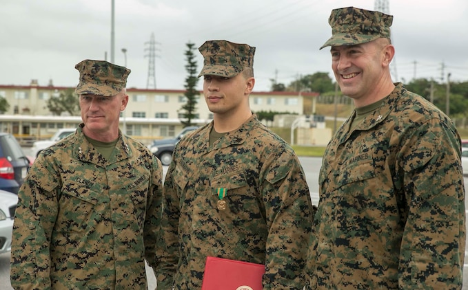"Maj. Gen. H. Stacy Clardy, left, Sgt. Jacob J. Baumann, center, and Col. Lance A. McDaniel, pose for a photo Jan. 14 after awarding Baumann the Navy and Marine Corps Achievement Medal for potentially saving the life of a local Japanese gentleman. ""It's our job as Marines to help everybody; I'm not one to have a lack of care for others, it's not my lifestyle,"" said Baumann, from Junction City, Kansas. Clardy is the commanding general of 3d Marine Division. Baumann is a fire support man with Headquarter Battery, 12th Marine Regiment, 3rd Marine Division, III Marine Expeditionary Force. McDaniel is the commanding officer of 12th Marine Regiment."