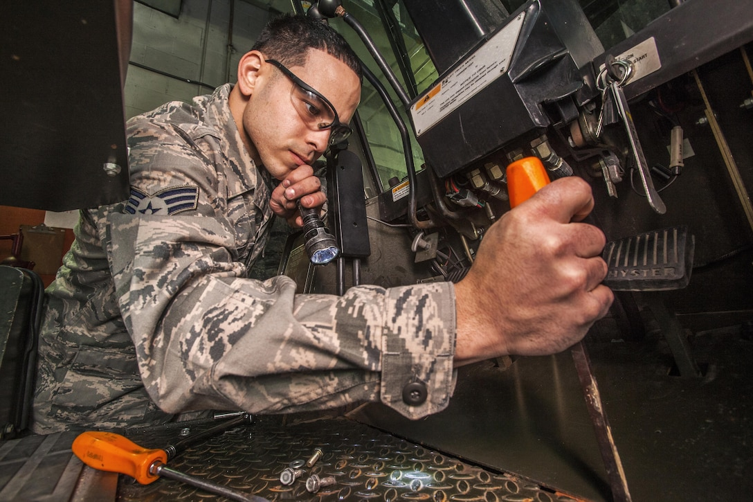 U.S. Air Force Tech. Senior Airman Christopher Garcia removes a panel to fix a neutral start switch on a 10K forklift at the 108th Wing Vehicle Maintenance Shop, New Jersey Air National Guard, at Joint Base McGuire-Dix-Lakehurst, N.J., Jan. 10, 2015. (U.S. Air National Guard photo by Master Sgt. Mark C. Olsen/Released)