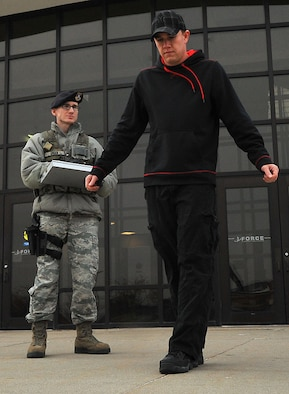 Senior Airman Caleb Green and Airman Bryce Willsey simulate the walk-and-turn portion of the field sobriety test Dec. 10, 2014, on Grand Forks Air Force Base, N.D. The FST consists of three different portions and is used to test a subject who is believed to be intoxicated. During the walk-and-turn portion, the subject is asked to walk nine steps in a straight line, heel-to-toe, and then turn around and walk in the opposite direction in the same fashion with the same number of steps. Green is a 319th Security Forces Squadron base defense operations control controller/patrolman. Willsey is a 319th SFS alarm monitor. (U.S. Air Force photo/Airman 1st Class Bonnie Grantham)
