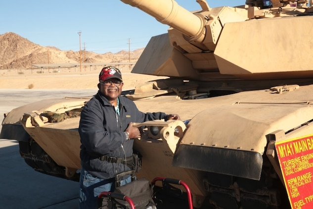 Kenny R. White, Marine veteran, native of San Diego, Calif., hugs a tank on the 1st Tank Battalion ramp, Dec. 22, 2014. White suffers from Stage 5-kidney failure and one of his most important final wishes was to hug a tank. (Official Marine Corps photo by Lance Cpl. Medina Ayala-Lo/Released)