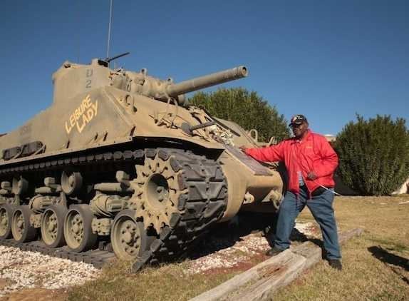 Kenny R. White, Marine veteran, native of San Diego, Calif., poses with a Sherman Tank outside of 1st Tank Battalion's headquarters building, Dec. 22, 2014. White received a tour of the M1A1 Abrams tank, and was able to see the Advance Gunnery Training Simulator as well. (Official Marine Corps photo by Lance Cpl. Medina Ayala-Lo/Released)