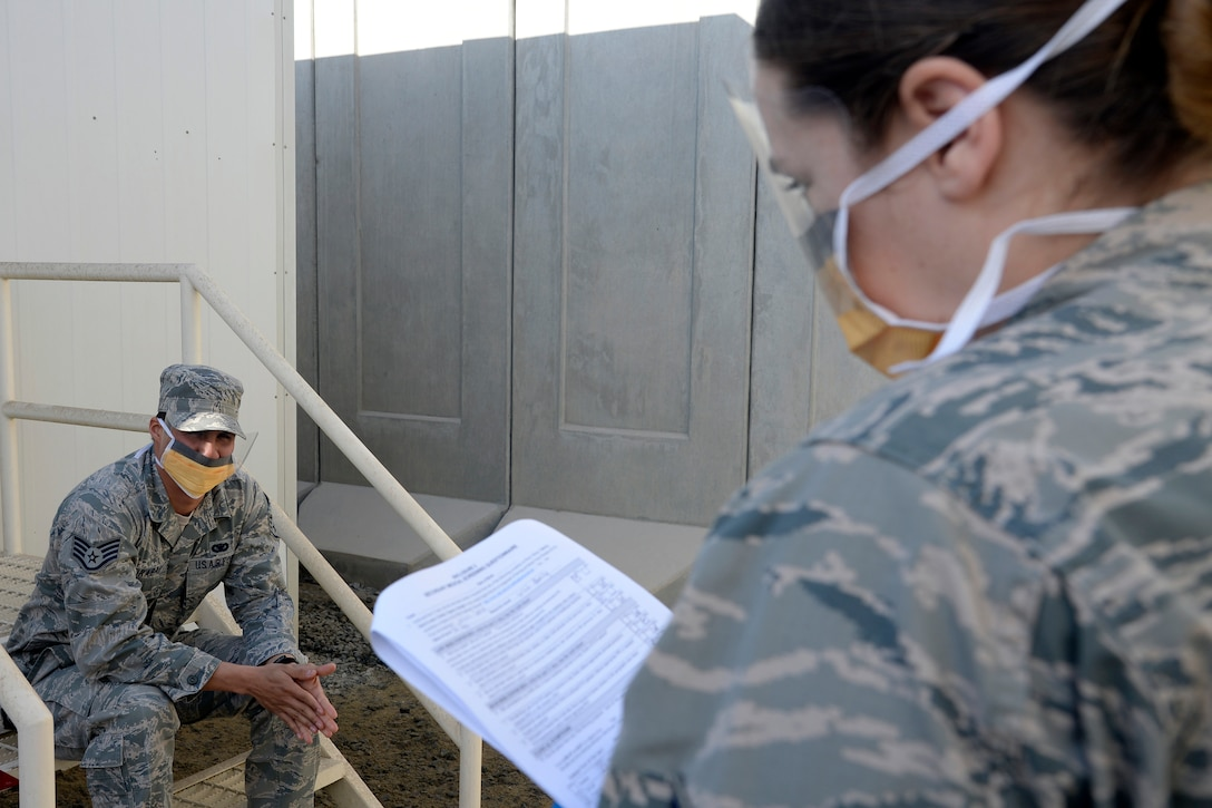 Staff Sgt. Hannah, medical technician, reviews a medical questionnaire with a possible Ebola patient during a training exercise at an undisclosed location in Southwest Asia Jan. 15, 2015. The exercise tested the Air Expeditionary Wing's Disease Containment Plan. Hannah is currently deployed from Joint Base Langley-Eustis, Va., and is a native of Lake Forest, Calif. (U.S. Air Force photo/Tech. Sgt. Marie Brown)