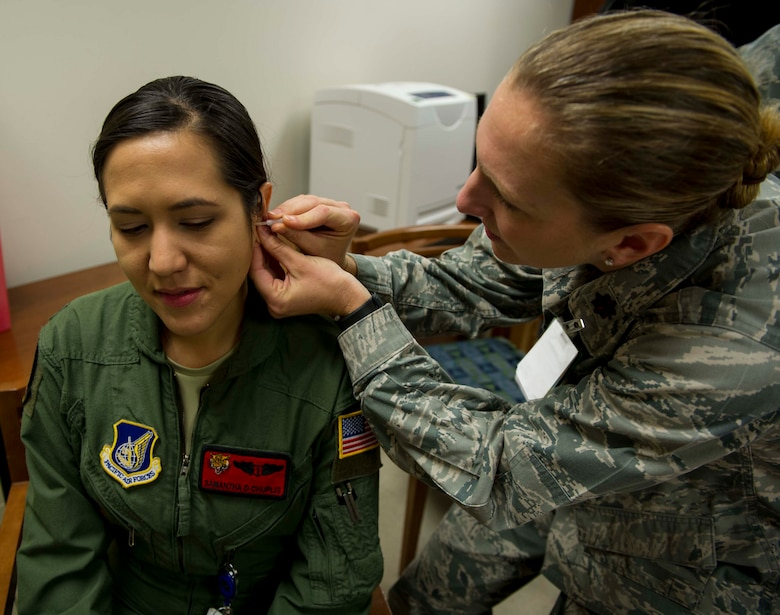 Maj. Katie Crowder, 15th Medical Group Family Health Clinic medical director, demonstrates the correct technique for battlefield acupuncture on Maj. Samantha Chuplis, 535th Airlift Squadron flight surgeon, during a refresher course for battlefield acupuncture at the 15th MDG at Joint Base Pearl Harbor-Hickam, Hawaii, Jan. 15, 2015. During the procedure up to five gold semi-permanent needles are placed into each ear. (U.S. Air Force photo by Tech. Sgt. Terri Paden)