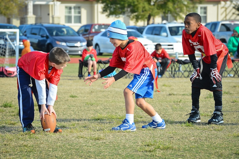 Children play flag football as part of the youth program's inaugural flag football season at MacDill Air Force Base, Fla., January 10, 2015. The youth program ensures the fields are maintained before every Saturday game, as well as paints the field, places the end zone pylons and trains referees to officiate the games. (U.S. Air Force photo by Senior Airman Ned T. Johnston/Released)