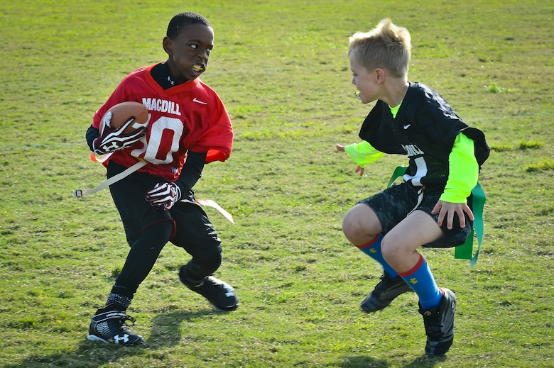 Two children play flag football as part of the youth program's inaugural flag football season at MacDill Air Force Base, Fla., January 10, 2015. On average, the youth programs have anywhere from 80 through 200 participants and has room to grow for new kids. (U.S. Air Force photo by Senior Airman Ned T. Johnston/Released)