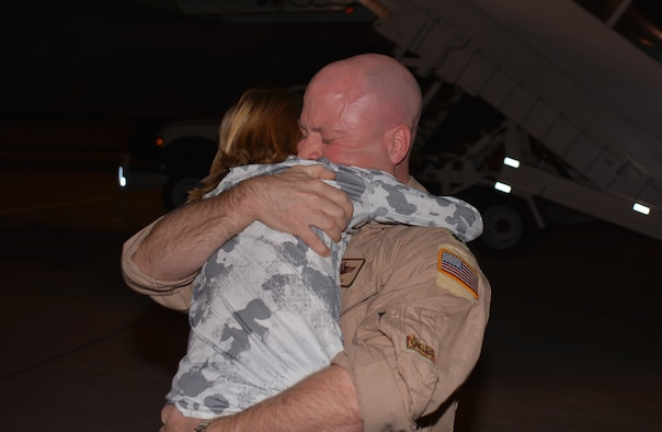 Lt. Col Benjamin Evans, 465th Air Refueling Squadron embraces his son after returning from a