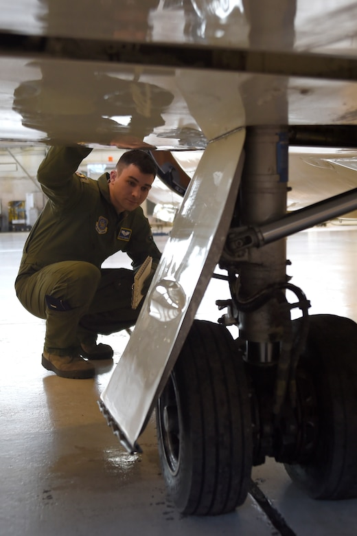 1st Lt. Jeff Morrow, 457th Airlift Squadron pilot, inspects landing gear during a pre-flight check of a C-21 on Joint Base Andrews, Md., Jan. 9, 2015. The inspector looks for: loose fittings, tires with tread separation, low inflation pressure, and other defects that could deem the aircraft unsafe. (U.S. Air Force photo/Airman 1st Class Ryan J. Sonnier)