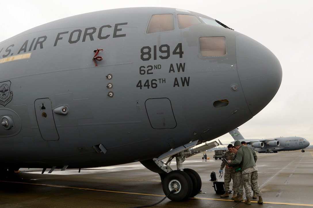 Airmen from the 62nd Aircraft Maintenance Squadron perform hydraulics maintenance on a C-17 Globemaster III Jan. 12, 2015 at Joint Base Lewis-McChord, Wash. The 62nd AMXS began using cross utilization training to certify four crew chiefs in hydraulics tasks to assist with low manning numbers in the hydraulics section.  (U.S. Air Force photo/ Staff Sgt. Tim Chacon)