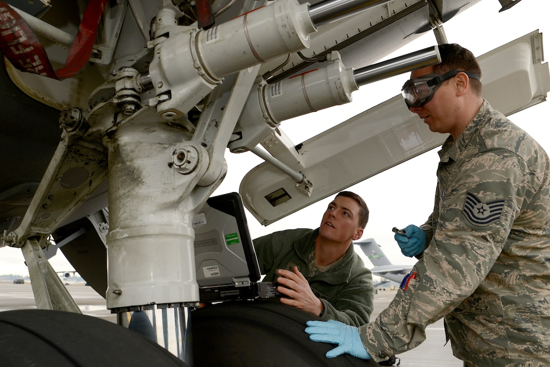 Staff Sgt. Dustin Michel, 62 Aircraft Maintenance hydraulics specialist (left) trains Tech. Sgt. Patrick Starkey, 62nd Aircraft Maintenance Squadron crew chief, on C-17 Globemaster III hydraulics maintenance, Jan. 12, 2015 at Joint Base Lewis-McChord, Wash. Starkey recently completed a four week cross utilization training course to supplement low manning numbers in the 62 AMXS hydraulics section. (U.S. Air Force photo/ Staff Sgt. Tim Chacon)
