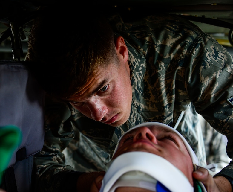U.S. Air Force Airman 1st Class Gregory Pease, 612th Air Base Squadron firefighter, braces U.S. Air Force Staff Sgt. Daniel Easterlund's neck during aircraft crash rescue training at Soto Cano Air Base, Honduras, Jan. 15, 2015.  At least once a quarter, the 612th ABS teams up with the 1-228th Aviation Regiment to review aircraft crash rescue training and emergency procedures for the UH-60 Blackhawk helicopter. (U.S. Air Force photo/Tech. Sgt. Heather Redman)