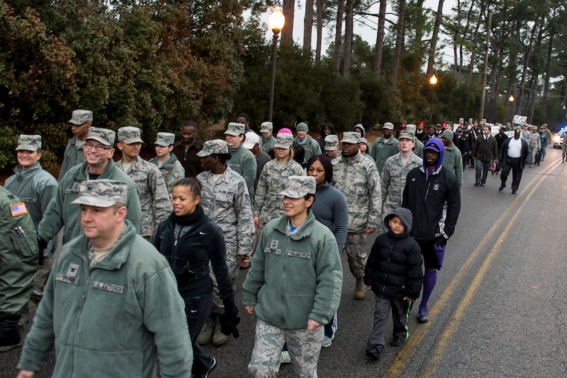 More than 100 service members, civilians and family members walk on Arthur Drive during a memorial march commemorating Martin Luther King Jr., Jan. 16, 2015, at Joint Base Charleston, S.C Following the march a celebratory program was held inside the chapel, with guest speaker Doug Hunter, the executive director of the Whitfield Center for Christian Leadership at Charleston Southern University. Martin Luther King Jr. Day is a federal holiday that celebrates his life and achievements as an influential leader of the American Civil Rights Movement.   (U.S. Air Force photo/Senior Airman Jared Trimarchi)
