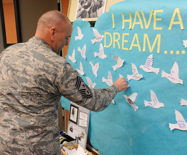 Chief Master Sgt. Darin Jones, 30th Space Wing command chief, places a paper dove representing his dream, on a dream board during a Martin Luther King, Jr. event, Jan. 15, 2015. Monday, Jan. 19, commemorates the life and achievements of Dr. Martin Luther King, Jr. The work he accomplished and his vision have permanently altered the country we live in today. (U.S. Air Force photo by Airman Robert J. Volio/Released)