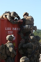 Marines with Engineer Platoon, Headquarters and Service Company, Ground Combat Element Integrated Task Force, assist each other in climbing over a storage container during a field training exercise at Engineer Training Area 2 aboard Marine Corps Base Camp Lejeune, North Carolina, Jan. 16, 2015. From October 2014 to July 2015, the GCEITF will conduct individual and collective level skills training in designated ground combat arms occupational specialties in order to facilitate the standards based assessment of the physical performance of Marines in a simulated operating environment performing specific ground combat arms tasks. (U.S. Marine Corps photo by Cpl. Paul S. Martinez/Released)