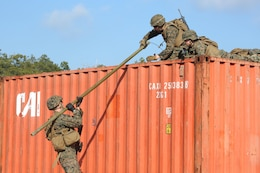 Cpl. Jordan M. Yearsley, left, combat engineer, Engineer Platoon, Headquarters and Service Company, Ground Combat Element Integrated Task Force, and Lance Cpl. Marshal P. Thompson, upper right, combat engineer, Engineer Platoon, H&S Company, GCEITF, transport an M1A2 Bangalore over an storage container during a field training exercise at Engineer Training Area 2 aboard Marine Corps Base Camp Lejeune, North Carolina, Jan. 16, 2015. From October 2014 to July 2015, the GCEITF will conduct individual and collective level skills training in designated ground combat arms occupational specialties in order to facilitate the standards based assessment of the physical performance of Marines in a simulated operating environment performing specific ground combat arms tasks. (U.S. Marine Corps photo by Cpl. Paul S. Martinez/Released)