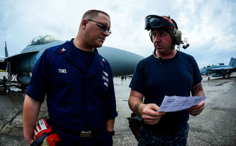 Petty Officer 2nd Classes Kyle McDonough and Benjamin Thiel, ordnance team leaders, discuss load plans while exercising at MacDill Air Force Base, Fla., Jan. 12, 2015.  McDonough and Thiel participated in a VFA-106 Navy Training Exercise that included the F-18 Hornet and Super Hornet jet aircraft from Oceana Naval Air Station, Va. (U.S. Air Force photo by Tech. Sgt. Brandon Shapiro/Released)