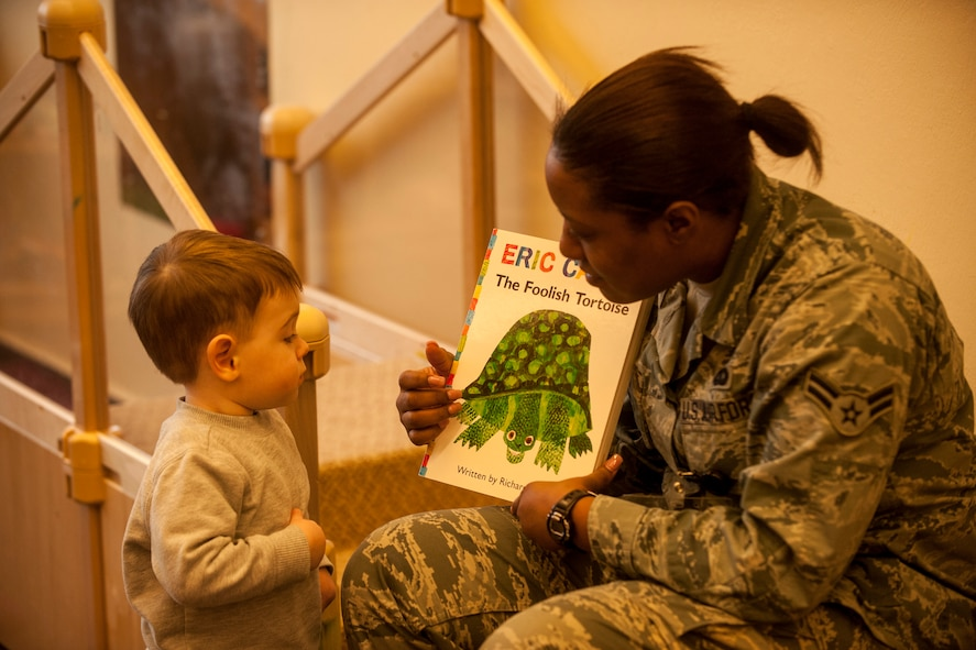 "U.S. Air Force Davida Sims, a 52nd Maintenance Group commander's support staff apprentice, displays a book to a child during the second annual Dr. Martin Luther King Jr. ""Reading is a Civil Right"" reading drive Jan. 15, 2015, at a child development center at Spangdahlem Air Base, Germany. More than 50 volunteers signed up for the event that was sponsored by the base's Airmen Against Drunk Driving council and the CDC. (U.S. Air Force photo by Senior Airman Rusty Frank/Released)"