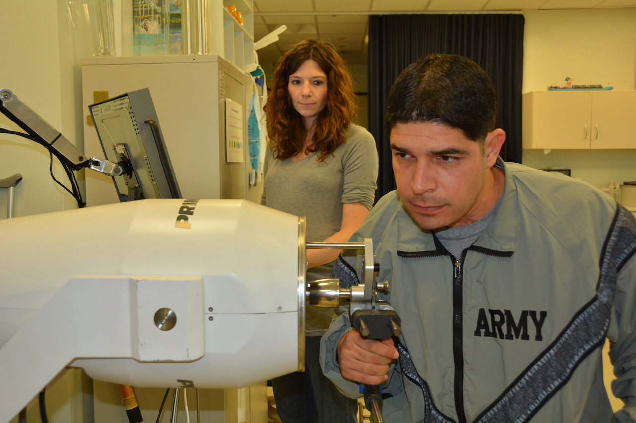 Army 1st Lt. John Arroyo works on strengthening his right hand while his occupational therapist, Katie Korp, looks on at the Center for the Intrepid, Brooke Army Medical Center's rehabilitation facility at Joint Base San Antonio-Fort Sam Houston, Jan. 16, 2015. Arroyo, severely wounded in a shooting at Fort Hood, hopes his story of survival will inspire others. U.S. Army photo by Robert Shields