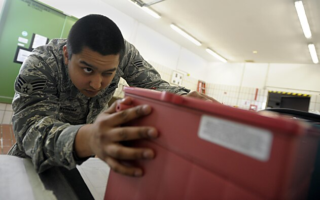 Senior Airman Gabriel Sundstrom checks for damage on a battery Jan. 15, 2015, at Ramstein Air Base, Germany. The electrical and environmental systems flight performs pre-flight and preventative maintenance on all aircraft and systems to keep them operational for mission readiness. Sundstrom is an 86th Maintenance Squadron electrical and environmental specialist. (U.S. Air Force photo/Senior Airman Timothy Moore)