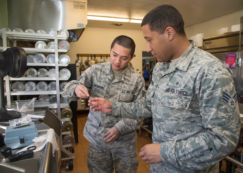 Staff Sgt. Harold King Pascual Tamondong and Senior Airman Andrew Travis add a reagent to a drinking water sample collected at the Child Development Center Youth Annex kitchen. The results will identify the level of chlorine present. Chlorine levels indicate how well the drinking water system disinfection process is operating. (U.S. Air Force photo by Ethan Wagner)