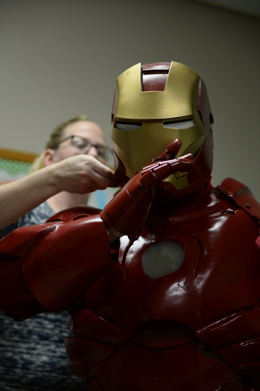 Tech. Sgt. Brian Thornton, 628th Air Base Wing air defense council paralegal, dons his homemade Iron Man suit with the help of his wife, Joy Thornton, Dec. 8, 2014 to visit students at Marrington Elementary, Joint Base Charleston - Weapons Station, S.C. The suit took Thornton ten months to complete and is made out of paper, car bondo, Plexiglas, nuts, bolts and anything else he could find in his garage. Thornton wears his Iron Man suit at local schools and hospitals hoping to help brighten a child's day. (U.S. Air Force photo/Senior Airman Christopher Reel)