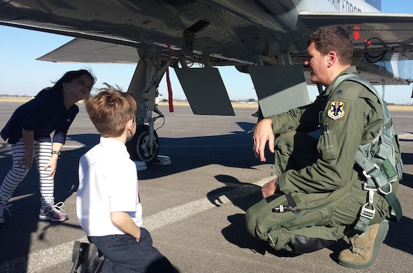 Lt. Col. Robert Lee, 560th Flying Training Squadron director of operations and also the first pilot to land at the Joint Base San Antonio-Randolph Seguin Auxiliary Airfield, gives a tour of the aircraft to Jack and Matty Foster during symbolic ribbon cutting event at JBSA-Randolph Seguin Auxiliary Airfield Jan. 20. The event signified the reopening of the airfield following a $12.4 million repaving and construction project that included replacing and grading the entire airfield, stabilizing existing soils, and constructing a new taxiway, parking apron and emergency access road.  (U.S. Air Force photo by Johnny Saldivar)