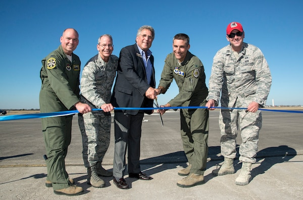 """Col. David Drichta, 12th Operations Group commander, Brig. Gen. Bob LaBrutta, 502nd Air Base Wing and Joint Base San Antonio commander, City of Seguin Mayor Don Keil, Col. Matt Isler, 12th Flying Training Wing commander; and Capt. Erich Kramer, 820th Rapid Engineers Deployable Heavy Operational Repair Squadron design engineer cut the ribbon signifying the reopening of the Joint Base San Antonio-Randolph Seguin Auxiliary Airfield Jan. 20.  Upon completion of a three-year construction project, the airfield is now ready for flying by members of the 560th Flying Training Squadron.  The airfield is crucial for """"touch and go"""" training that qualifies fighter and bomber pilots as instructor pilots in the T-38C Talon.  The reconstructed runway increases flight safety by distributing training around the San Antonio area, which means fewer aircraft and less congestion around Joint Base San Antonio-Randolph. (U.S. Air Force photo by Johnny Saldivar)"""