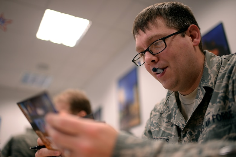An Airman participates in a Four Lenses personality assessment Jan. 14, 2015, in the 52nd Force Support Squadron's Airman and Family Readiness Center at Spangdahlem Air Base, Germany. During this assessment, the participants had to review different photographs and phrases that best describe their personality. Then, the participants were separated into four colors — blue for people who value relationships; green for competency; orange for freedom; and gold structure. (U.S. Air Force photo by Staff Sgt. Daryl Knee/Released)