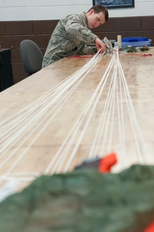 Senior Airman Mark Peterson, 51st Operations Support Squadron aircrew flight equipment journeyman, attaches a four line release lanyard onto a parachute at Osan Air Base, Republic of Korea, Jan. 20, 2015. The four line lanyards are used to help ster the parachute as well as relese air from the canopy. (U.S. Air Force photo by Senior Airman Matthew Lancaster)