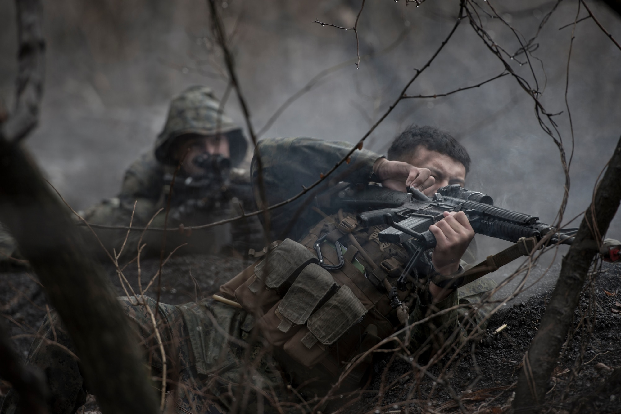 """A Marine with the 1st Batallion, 1st Marines, pulls the firing bolt on his weapon while in a simulated small-arms fire exchange Jan. 16, 2015 at Camp Fuji, Japan. The Marines, who were acting as enemy aggressors searching for Air Force aircrew during survival, evasion, resistance and escape training, also practiced their small arms engagement with a """"rescue"""" team of Marines. (U.S. Air Force photo/Staff Sgt. Cody H. Ramirez)"""