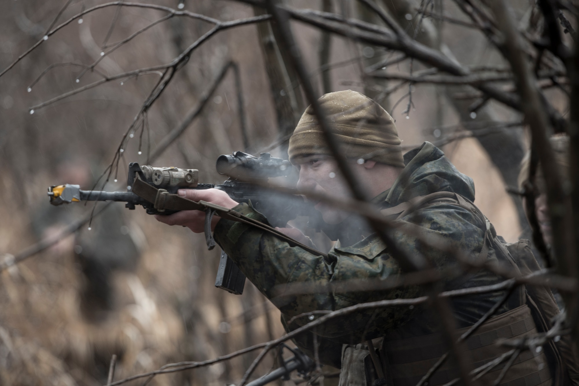 """A Sailor with the 1st Batallion, 1st Marines, simulates weapon fire shooting blanks toward escaping aircrew members during joint training Jan. 16, 2015 at Camp Fuji, Japan. The Marines, who were acting as enemy aggressors searching for Air Force aircrew during survival, evasion, resistance and escape training, also practiced their small arms engagement with a """"rescue"""" team of Marines. (U.S. Air Force photo/Staff Sgt. Cody H. Ramirez/)"""