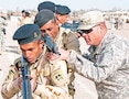 "Sgt. David Kappel (right), an infantry trainer assigned to Company A, 2nd Battalion, 34th Armor Regiment, 1st Armored Brigade Combat Team, 1st Infantry Division, adjusts the rifle of an Iraqi army trainee as he instructs the soldiers how to properly stack in preparation to move toward their objective Jan. 7 at Camp Taji, Iraq. Kappel is one of more than 150 ""Dreadnaughts"" of 2nd Bn., 34th Armor Regt., who are advising several Iraqi army battalions, providing new recruits advanced training and assisting Iraqi cadre by teaching small unit tactics and leadership. 