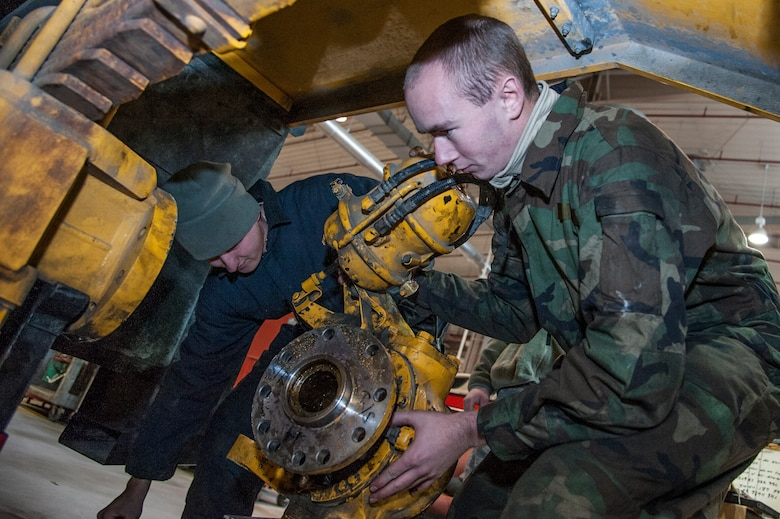 Airman 1st Class Chris O'Connor, 51st Logistics Readiness Squadron special purpose vehicle maintenance apprentance, and Airman 1st Class James Johnson, 51st LRS special purpose vehicle maintenance journeyman, take the hub assembley off a street sweeper at Osan Air Base, Republic of Korea, Dec. 22, 2014. In order to change out a broken inter axel seal, the hub assembley on each side of the street sweeper had to be taken off. (U.S. Air Force photo by Senior Airman Matthew Lancaster)