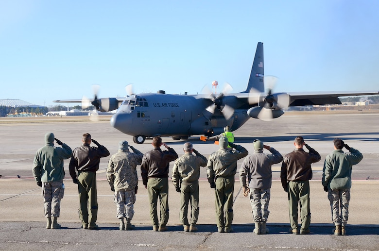 Dobbins Air Reserve Base leadership salutes the aircrew as the 94th Airlift Wing Hercules begins to taxi out for takeoff to Southwest Asia, at Dobbins Air Reserve Base, Ga., Jan. 8, 2015. (U.S. Air Force photo/Brad Fallin)