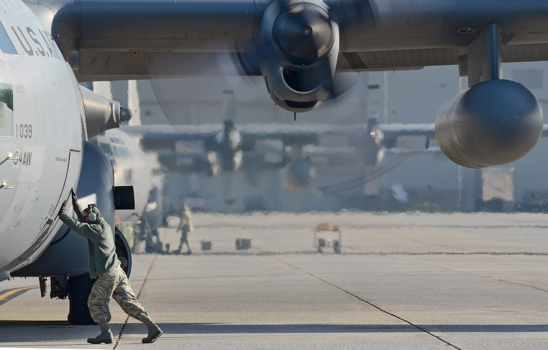 C-130H Crew Chief Senior Airman David Yancey ensures the forward doorway is closed as the 94th Airlift Wing Hercules is nearly ready to deploy to Southwest Asia, Jan. 5, 2015. (U.S. Air Force photo/Brad Fallin)