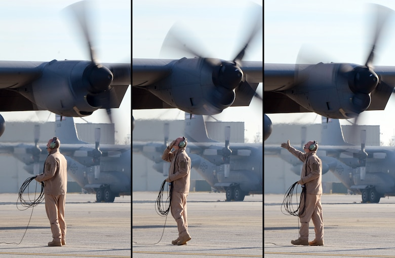 After all four engines have started Stan Eval Loadmaster, Senior Master Sgt. Bill Hutchinson says goodbye to his family, observing from the fence line, as the 94th Airlift Wing Hercules is nearly ready to deploy to Southwest Asia, Jan. 5, 2015. (U.S. Air Force photo/Brad Fallin)